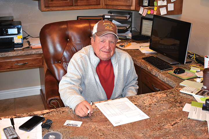 Dennie Arnold gets some early-morning work done in his office.